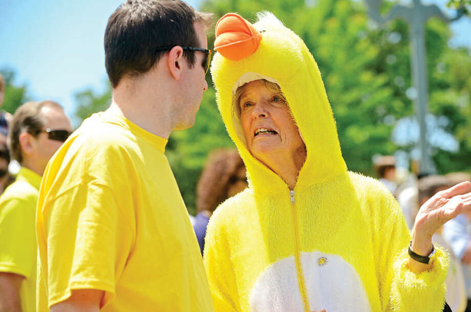 Hour photo / Erik Trautmann Sunrise Rotarians Frank Hackett and Diane Cady chat during the Westport Sunrise Rotary's annual Great Duck Race event at the Saugatuck River in downtown Westport Saturday.