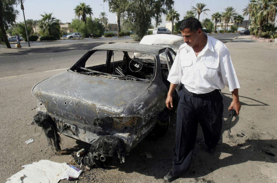 FILE - This Sept. 25, 2007 file photo shows an Iraqi traffic policeman inspecting a car destroyed by a Blackwater security detail in al-Nisoor Square in Baghdad, Iraq. In a tale of death and destruction, a federal prosecutor has chronicled for a jury the alleged conduct of four Blackwater security guards accused of killing 14 Iraqis and wounding 18 others in downtown Baghdad nearly seven years ago. In opening statements Tuesday at the trial of the four guards, Assistant U.S. Attorney T. Patrick Martin said the victims were simply trying to get out of the way of gunfire from the Blackwater guards. (AP Photo/Khalid Mohammed, File)