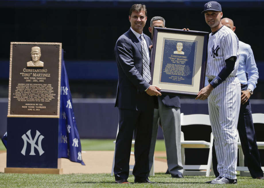 Former New York Yankees first baseman Tino Martinez, left, poses with shortstop Derek Jeter (2) and a replica of a plaque dedicated to his time with the Yankees before of a baseball game against the Baltimore Orioles, Saturday, June 21, 2014, in New York. The plaque, left, will hang at the stadium's Monument Park. (AP Photo/Julie Jacobson)