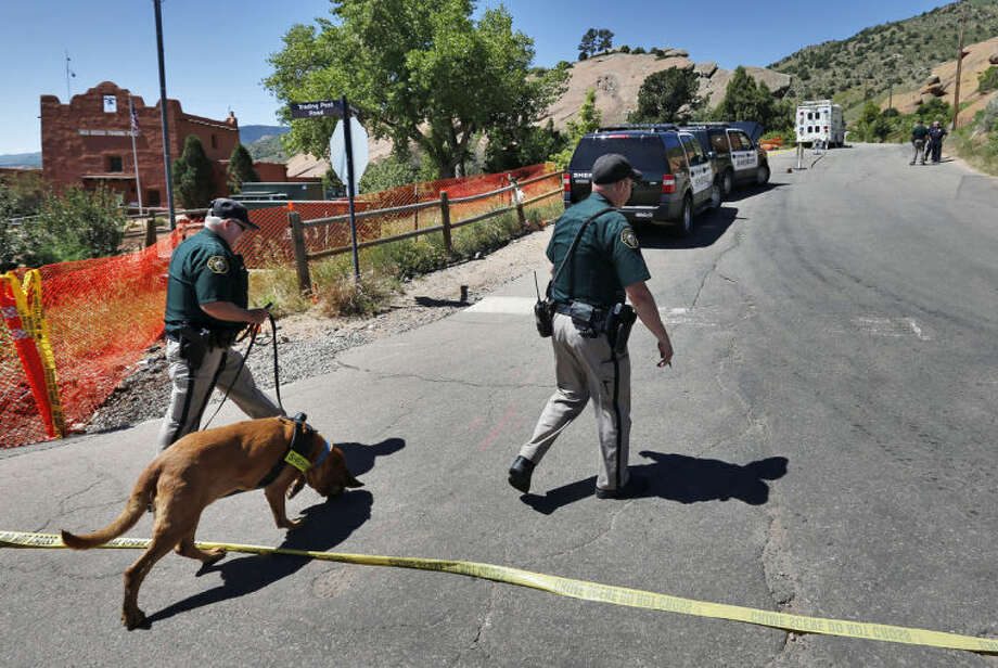 A police K-9 team walks into the closed off south entrance to Red Rocks Amphitheater, in Morrison, Colo., Friday June 20, 2014. Authorities were searching Friday for a gunman who shot and wounded three people at the end of a benefit concert at the popular outdoor amphitheater near Denver on June 19. (AP Photo/Brennan Linsley)