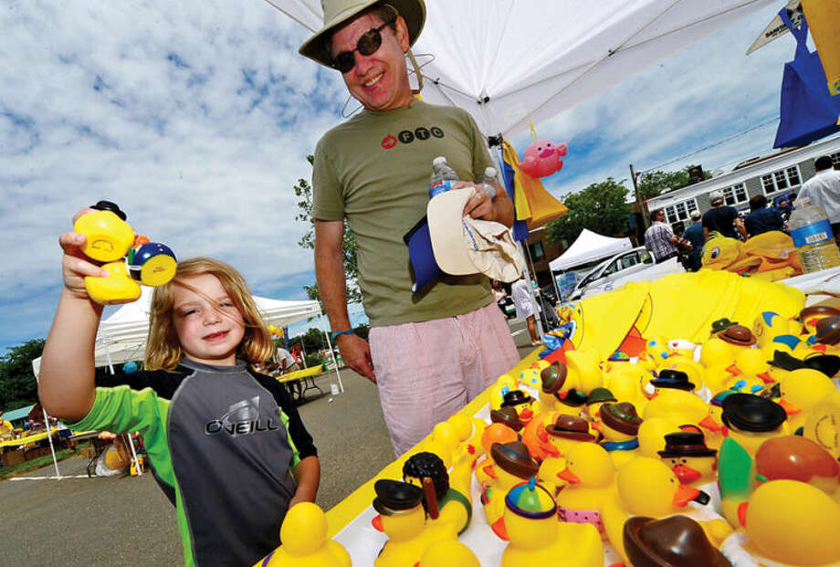 Hour photo / Erik Trautmann 5 year old Ella Manchester gets three rubber duckies while he visits the Westport Sunrise Rotary's annual Great Duck Race event with dad, Jeff Manchester, at the Saugatuck River in downtown Westport Saturday.