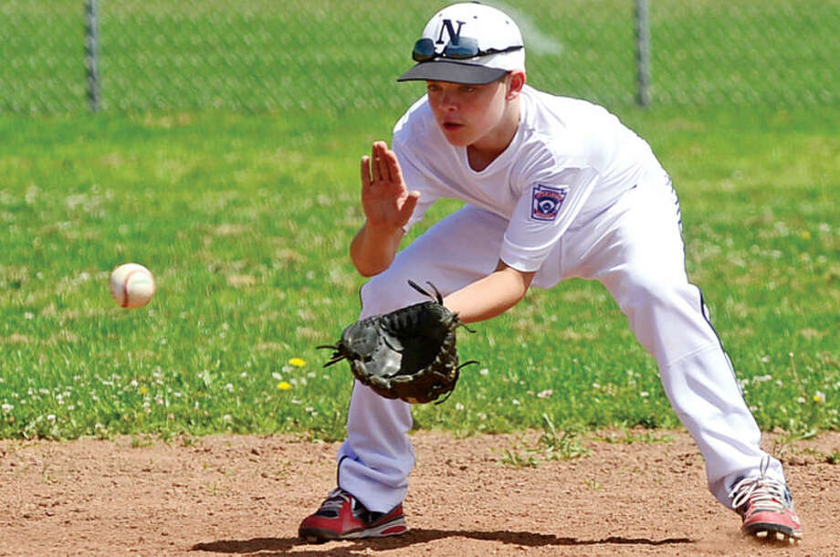 Hour photo / Erik Trautmann Jack Matthews fields a ball during the Norwalk Little League All-Star team practice at Veteran's Park Saturday.