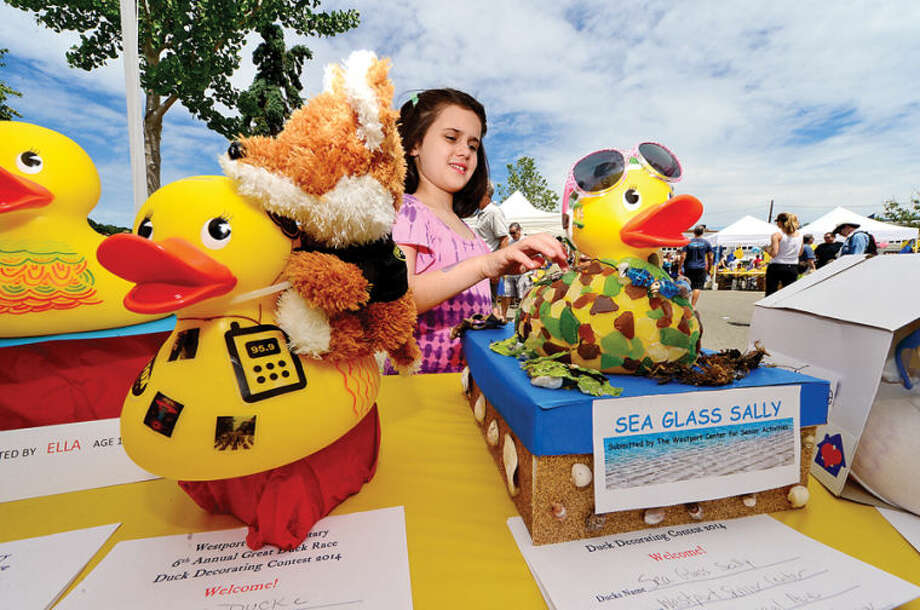 Hour photo / Erik Trautmann Abby Dellavalle, 9, looks over the rubber duckie decorating contest entries during the Westport Sunrise Rotary's annual Great Duck Race event at the Saugatuck River in downtown Westport Saturday.