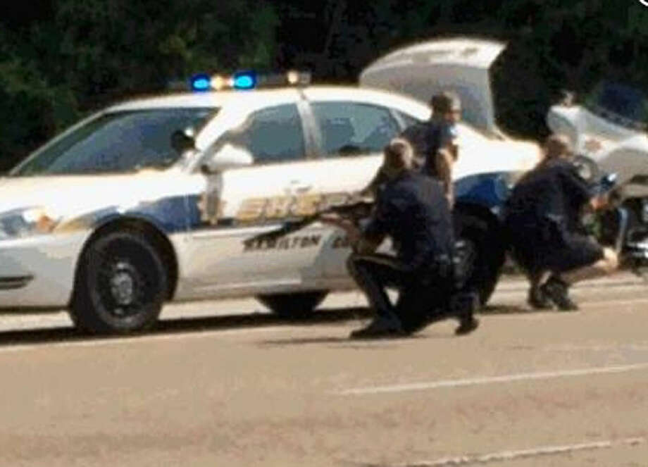 In this image made from video and released by WRCB-TV, authorities work an active shooting scene on amincola highway near the Naval Reserve Center, in Chattanooga, Tenn. on Thursday, July 16, 2015. Chattanooga Mayor Andy Berke says police are pursuing an active shooter after reports of a shooting at the military reserve center. (WRCB-TV via AP) MANDATORY CREDIT