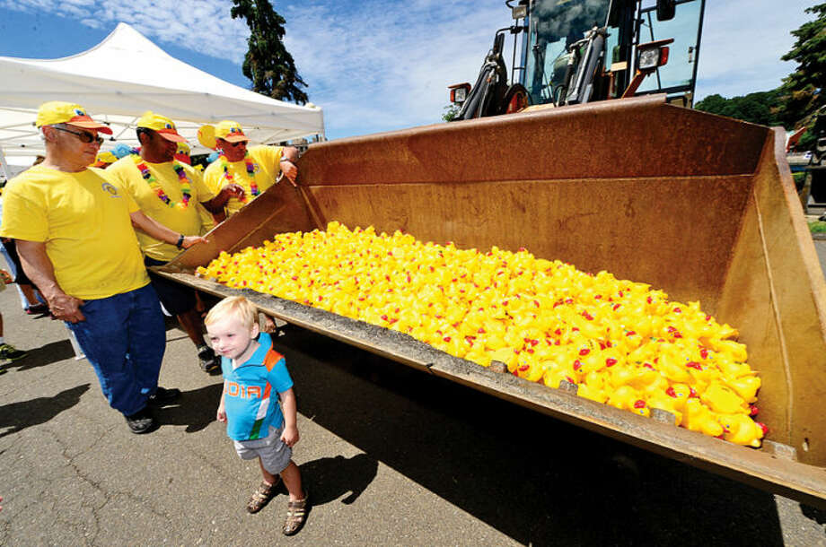 Hour photo / Erik Trautmann 2 year old James Scmidt poses near 2,500 rubber duckie entrants in the Westport Sunrise Rotary's annual Great Duck Race event at the Saugatuck River in downtown Westport Saturday.