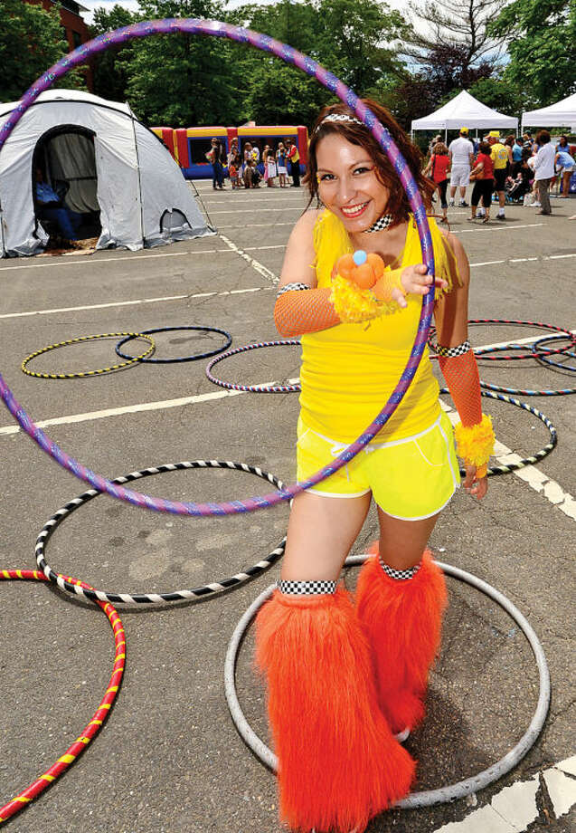 Hour photo / Erik Trautmann Veronica Vixen twirls her hula hoops during the Westport Sunrise Rotary's annual Great Duck Race event at the Saugatuck River in downtown Westport Saturday.