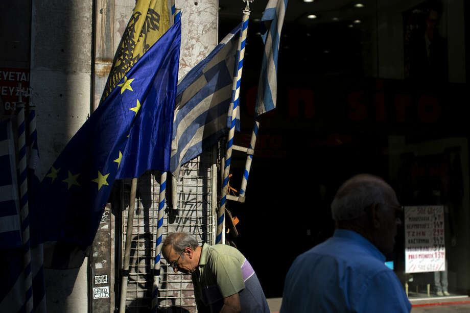 People walk past a shop selling flags of Greece and European Union in central Athens, Thursday, July 16, 2015. Greece's troubled left-wing government is seeking urgent relief from European lenders on Thursday, after it pushed a harsh austerity package thought parliament, triggering a revolt in the ruling party and violent demonstrations in central Athens. (AP Photo/Emilio Morenatti)