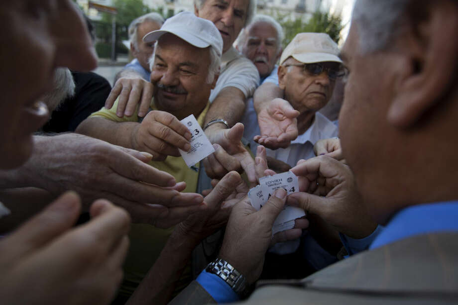 A bank employee distributes tags with queue positions to pensioners as they wait outside the main gate of the national bank of Greece to withdraw a maximum of 120 euros ($134) in central Athens, Thursday, July 16, 2015. Greece's troubled left-wing government is seeking urgent relief from European lenders on Thursday, after it pushed a harsh austerity package thought parliament, triggering a revolt in the ruling party and violent demonstrations in central Athens. (AP Photo/Emilio Morenatti)