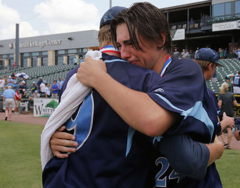 San Antonio Johnson's Bryce Faust (9) and Jaydan Martinez (24) hug after their team fell to Dallas Jesuit 6-2 during the UIL State Baseball 6A championship in Round Rock Saturday, June 11, 2016. Photo: Stephen Spillman