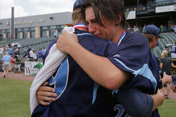 San Antonio Johnson's Bryce Faust (9) and Jaydan Martinez (24) hug after their team fell to Dallas Jesuit 6-2 during the UIL State Baseball 6A championship in Round Rock Saturday, June 11, 2016.