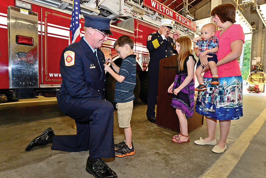 Firefighter Brian Elliott is pinned by his son, Jackson, 6, while his wife, Renee, his daughter, Abigail, and his infant son, Jacob, look on.