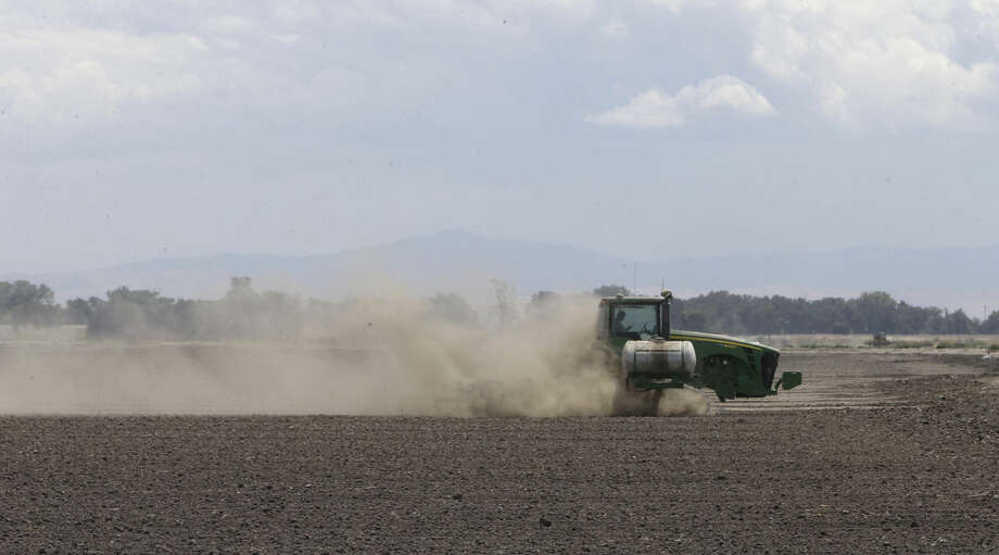 FILE -- In this May 18, 2015 file photo, a tractor tills the dry land on the acreage farmed by Gino Celli, who relies on senior water rights to water his crops, near Stockton, Calif. California issued its first cease-and-desist order on Thursday, July 16, telling an irrigation district to stop pumping water under this year's tightened drought regulations. Some senior water rights holders are challenging California regulators authority to tell them to stop drawing water from rivers running dry due to the drought. (AP Photo/Rich Pedroncelli,file)