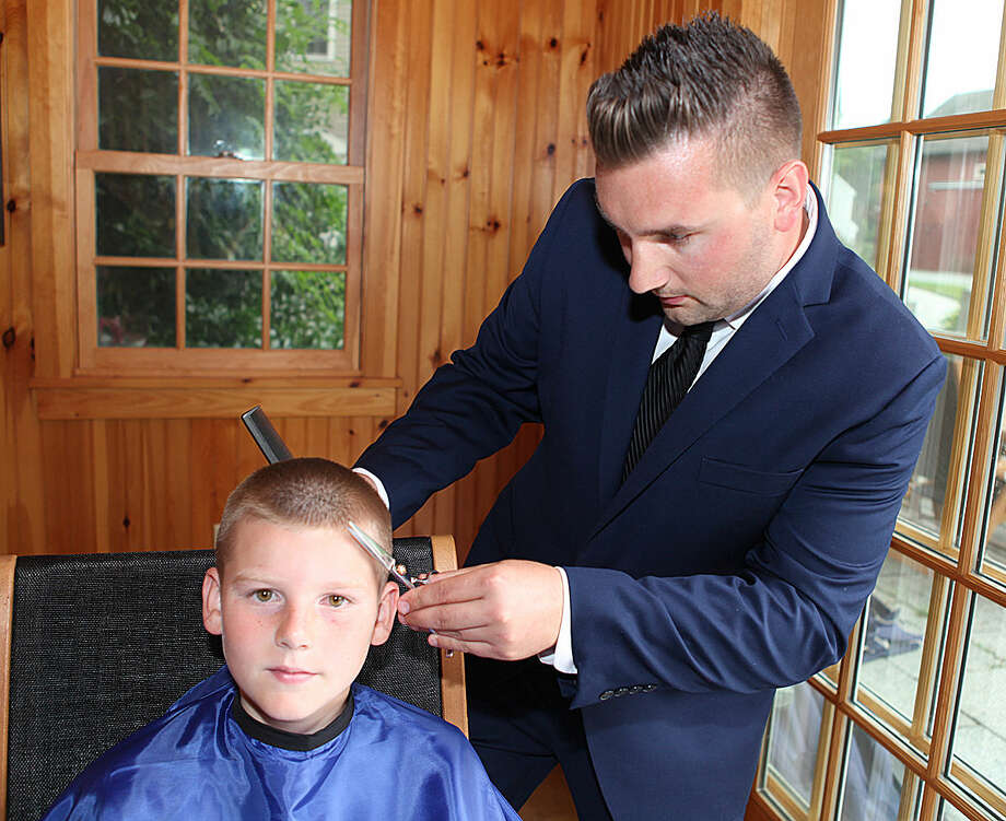 Photo by Mike Donnarummo photography Christian Iannucci of Doorbell Barbers cuts the hair of Hunter Stolze of Oxford. Iannucci has started a house-call hair cutting business.