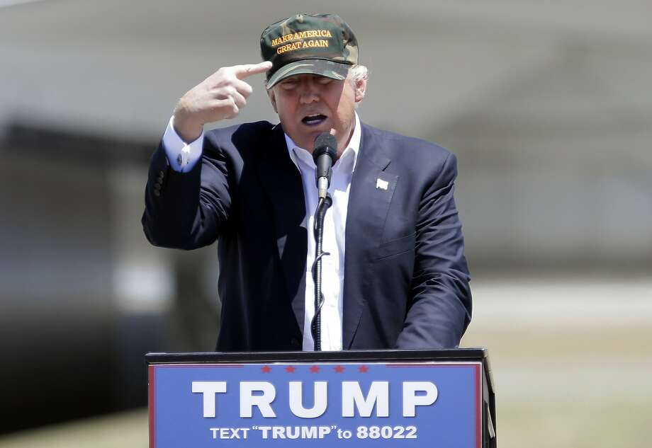 "In this June 3, 2016, photo, Republican presidential candidate Donald Trump gestures to a his camouflaged ""Make America Great"" hat as he discuses his support by the National Rifle Association at a campaign rally at the Redding Municipal Airport in Redding, Calif. Photo: Rich Pedroncelli, Associated Press"