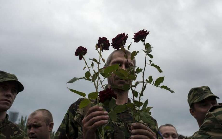 A pro-Russian fighter holds roses after taking the oath of allegiance to the self-proclaimed Donetsk People's Republic, on Lenin square in Donetsk, eastern Ukraine, Saturday, June 21, 2014. Dozens of pro-Russian armed militiamen gathered on Lenin square in Donetsk on Saturday to take the oath of allegiance to the so-called Donetsk People's Republic after Ukrainian President Petro Poroshenko ordered his forces to cease fire Friday and halt military operations for a week. (AP Photo/Evgeniy Maloletka)
