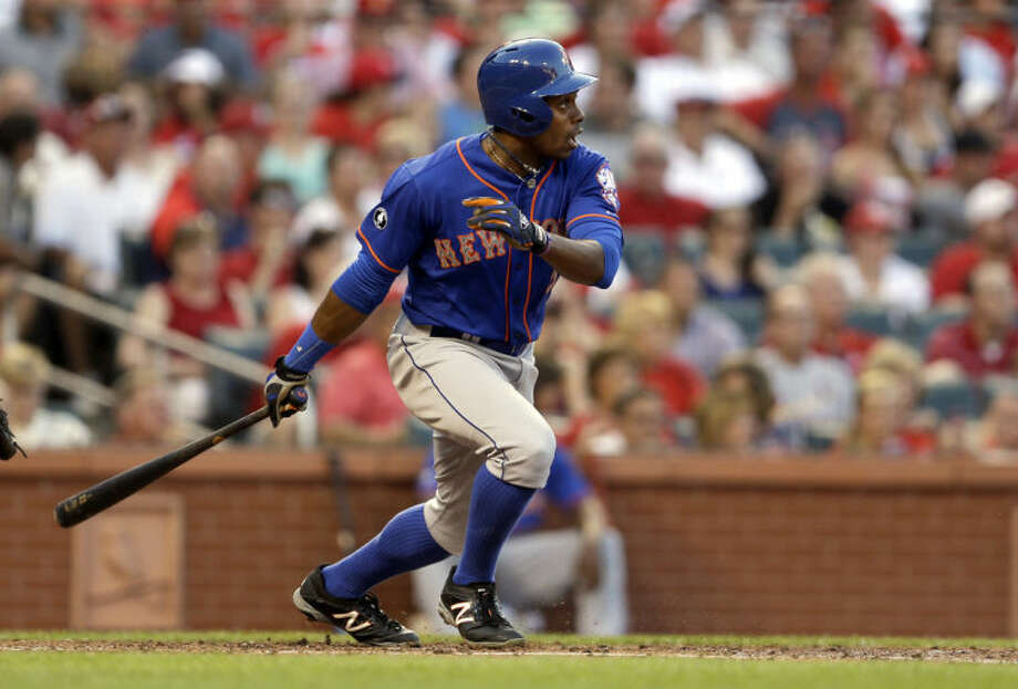 New York Mets' Curtis Granderson watches his sacrifice fly that scored Ruben Tejada during the third inning of a baseball game against the St. Louis Cardinals Monday, June 16, 2014, in St. Louis. (AP Photo/Jeff Roberson)