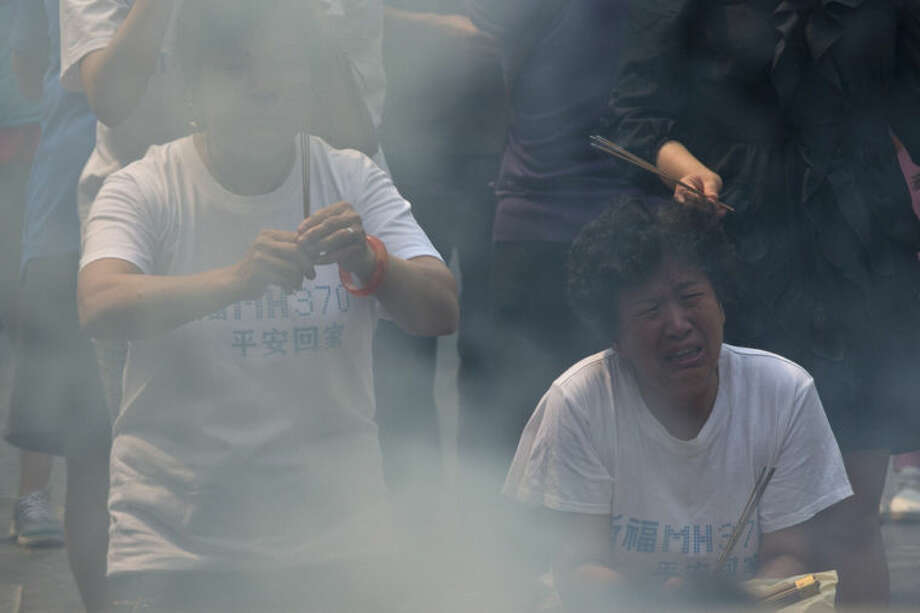 """In this June 15, 2014 photo, relatives of Chinese passengers on board the missing Malaysia Airlines Flight 370 cry as they burn incense to pray for their loved ones, on the 100th day after the flight went missing, at the Lama Temple in Beijing. Chinese characters on their T-shirts read: """"Pray for MH370. Come home safely."""" The absence of proof of death has made any closure elusive for the relatives of the 239 men and women on the plane. (AP Photo/Alexander F. Yuan)"""