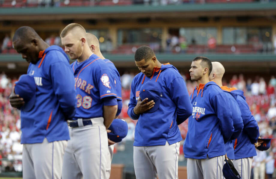 Members of the New York Mets pause during a moment of silence for former San Diego Padres baseball player Tony Gwynn before the start of a baseball game against the St. Louis Cardinals Monday, June 16, 2014, in St. Louis. Gwynn died early Monday morning of cancer at the age of 54. (AP Photo/Jeff Roberson)