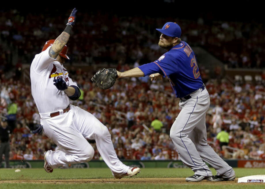 St. Louis Cardinals' Yadier Molina, left, is tagged out by New York Mets first baseman Lucas Duda to end the seventh inning of a baseball game Monday, June 16, 2014, in St. Louis. (AP Photo/Jeff Roberson)