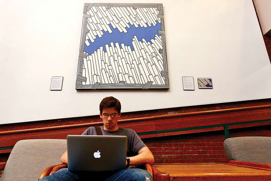 Norwalk Community College student Rafael Almeida studies under the newly restored Nicholas Krushenick painting, Flypath 1, that is being exhibited in the East Campus gallery.