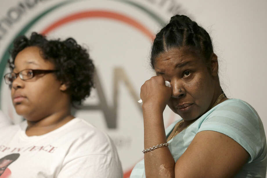 Eric Garner's wife Esaw Snipes, right, wipes a tear from her eye as she stands with daughter Emerald Snipes during a news conference, Tuesday, July 14, 2015, in New York. The family of Garner, a black man who died after being placed in a white police officer's chokehold, discussed the $5.9 million settlement it reached with the city days before the anniversary of his death. (AP Photo/Mary Altaffer)