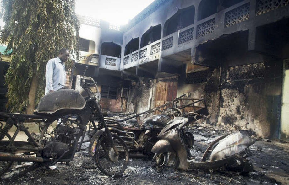 A man observes the remains of destroyed vehicles and buildings in the town of Mpeketoni, about 60 miles (100 kilometers) from the Somali border on the coast of Kenya Monday, June 16, 2014. Dozens of Somali extremists wielding automatic weapons attacked the small Kenyan coastal town for hours, assaulting the police station, setting two hotels on fire, and spraying bullets into the street killing dozens, officials said Monday. (AP Photo)