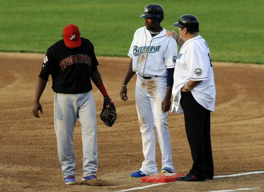 Pete Rose, right, talks with Bridgeport Bluefish's James Simmons, center, as Lancaster Barnstormers' Wilson Batista, right, stands by, Monday, June 16, 2014, in Bridgeport, Conn. Rose, banned from Major League Baseball, returned to the dugout for one day to manage the independent minor-league Bridgeport Bluefish. (AP Photo/Jessica Hill)