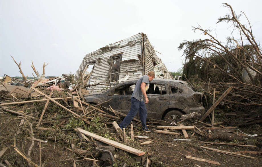 Tim Nelson searches for survivors in Pilger, Neb., after the town was hit by a tornado Monday June 16, 2014. Ast least one person has died due to the storm. (AP Photo/The Omaha World-Herald/Ryan Soderlin) MAGS OUT; ALL NEBRASKA LOCAL BROADCAST TV OUT