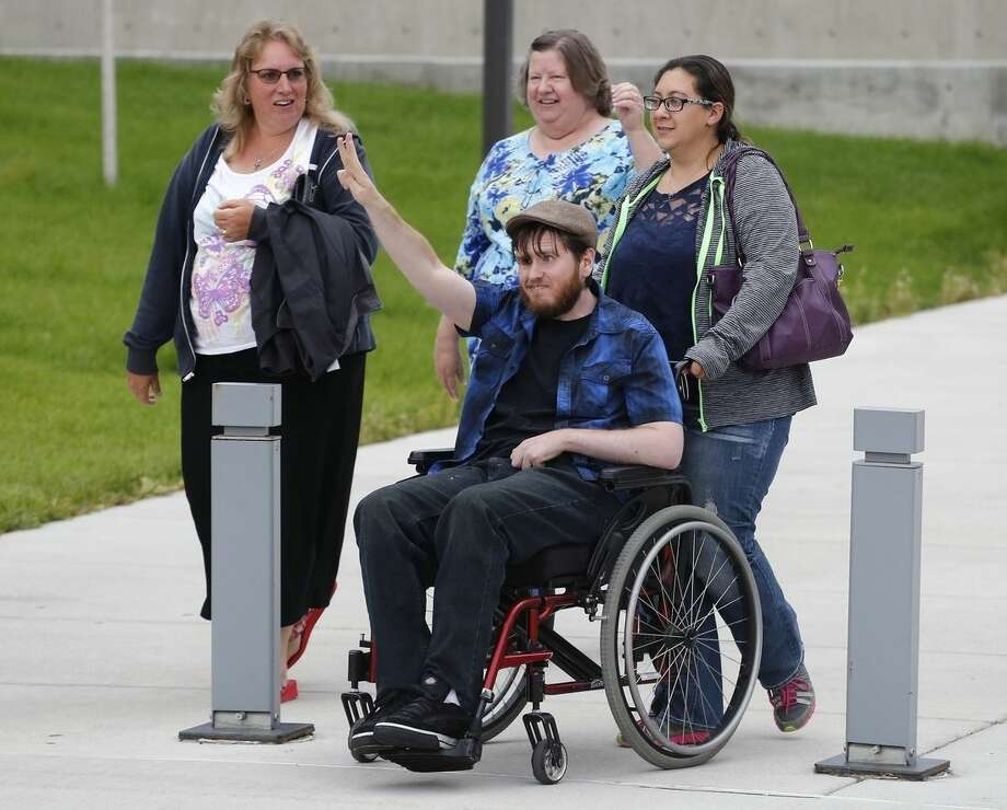 Katie Medley wheels her husband Caleb Medley, who was shot in the face in the 2012 Aurora movie theatre massacre, suffering paralysis and major brain trauma, as the two exit the Arapahoe County District Court accompanied by unnamed supporters following the day of closing arguments in the trial of theater shootings defendant James Holmes, in Centennial, Colo., Tuesday July 14, 2015. Katie Medley was also in the theater during the attack, and was 9-months pregnant at the time. (AP Photo/Brennan Linsley)