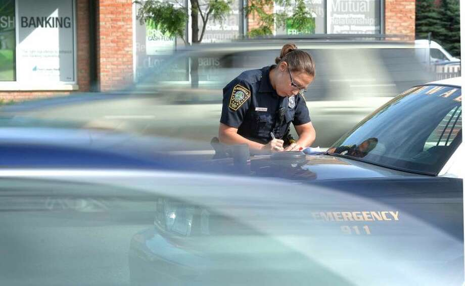 Hour Photo/Alex von Kleydorff Norwalk Police Officer Kelly Hollister writes up a ticket on the back of her cruiser parked with others in the turning lanes as cars stream past her on Connecticut Ave while police from Norwalk New Canaan and Wilton which are part of the multi-agency traffic safety task force that set up a distracted driving check point on Connecticut Ave Monday morning.