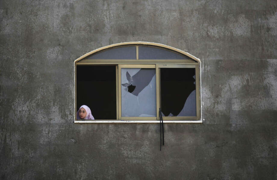 A Palestinian girl looks at a damaged home after it was hit by an Israeli missile strike in Gaza City, early Monday, June 16, 2014. Israel's military said it carried out airstrikes on five weapons and militant sites in Gaza, following overnight rocket fire from the coastal strip into Israel. Two rockets were intercepted and a third fell in an open area in Israel, causing no injuries, the military said. (AP Photo/Hatem Moussa)
