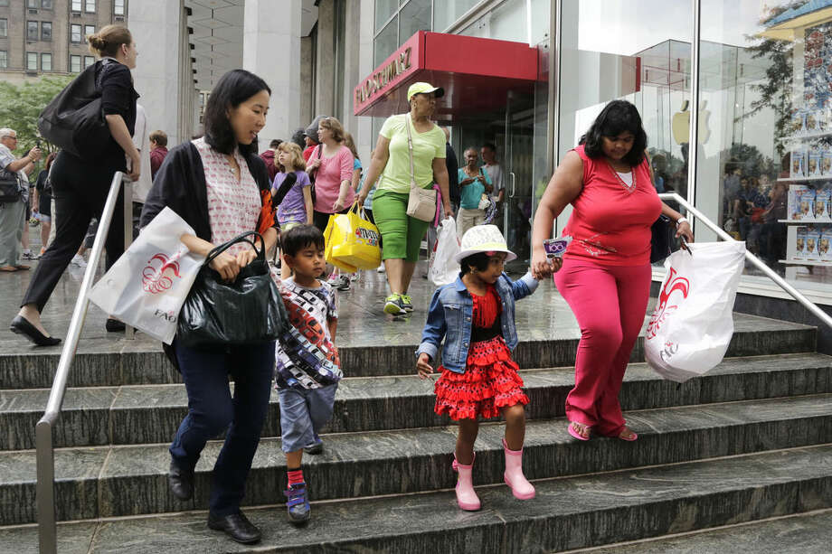 Women and children walk with packages outside of the flagship FAO Schwarz toy store on Fifth Avenue in New York, Wednesday, July 15, 2015. The store, probably the best-known toy store in the world, is closing Wednesday night. (AP Photo/Mark Lennihan)