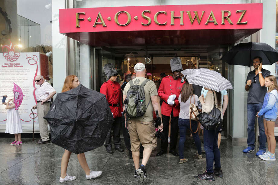 """Two """"toy soldiers"""" in bright red coats greet customers in front of the flagship FAO Schwarz toy store on Fifth Avenue in New York, Wednesday, July 15, 2015. The store, probably the best-known toy store in the world, is closing Wednesday night. (AP Photo/Mark Lennihan)"""