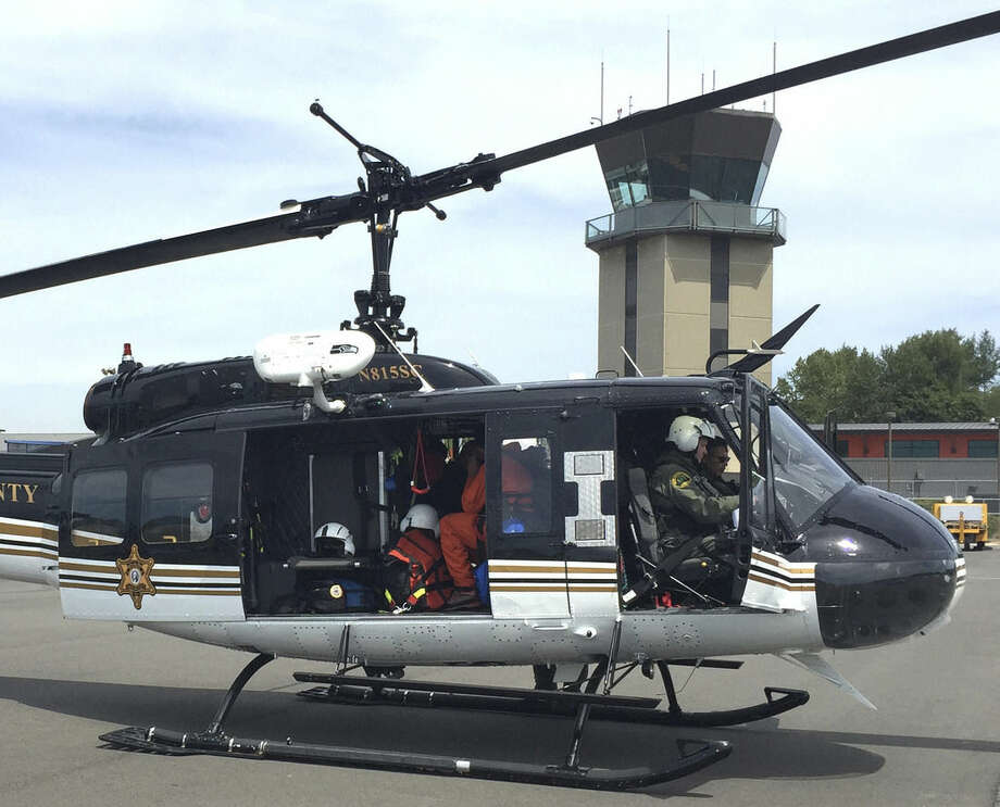 In this photo provided by the Civil Air Patrol, a Snohomish County Sheriff's Dept. helicopter is prepared for take off Tuesday, July 14, 2015, in Bellingham, Wash., to aid in the search for a plane that crashed Saturday with three people on board. One of the passengers, Autumn Veatch survived and was picked up by a motorist Monday after walking out of the rugged and remote crash site, but the search for the plane continued Tuesday. (Lt. Col. Jeffrey A. Lustick/Civil Air Patrol via AP)