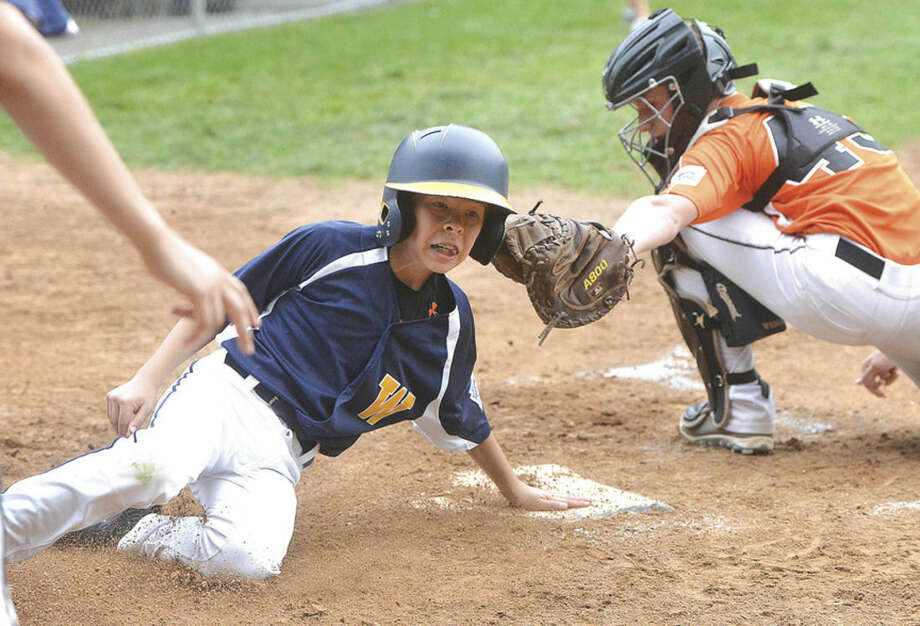 Hour photo/Alex von KleydorffWeston's Myles Lehrman slides safely into home plate in Weston's 18-11 win over Ridgefield. Weston will play against Stamford North in the District 1 Little League championship game on Friday.