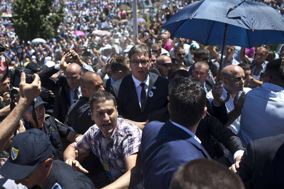 Aleksandar Vucic, Serbia's prime minister, center, is seen during a scuffle at the Potocari memorial complex near Srebrenica, 150 kilometers northeast of Sarajevo, Bosnia and Herzegovina, Saturday, July 11, 2015. Vucic was forced to flee after hundreds of people that gathered to commemorate the 20th anniversary of the Srebrenica massacre hurled stones, water bottles and insults at him. (AP Photo/Marko Drobnjakovic)