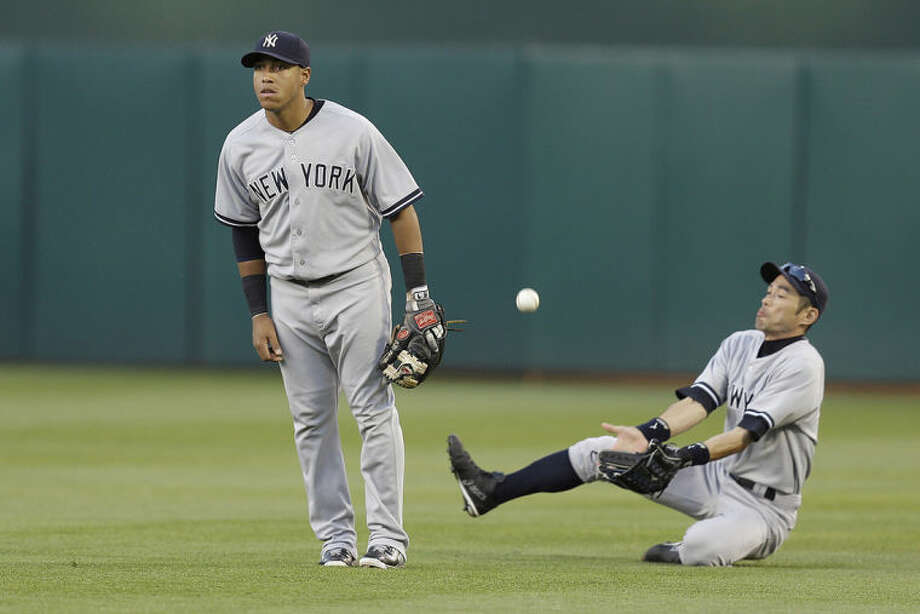 New York Yankees' Ichiro Suzuki, right, slides to make the catch on a ball hit by Oakland Athletics' Coco Crisp in the second inning of a baseball game on Saturday, June 14, 2014, in Oakland, Calif. Yankees second baseman Yangervis Solarte, left, looks on. (AP Photo/Ben Margot)