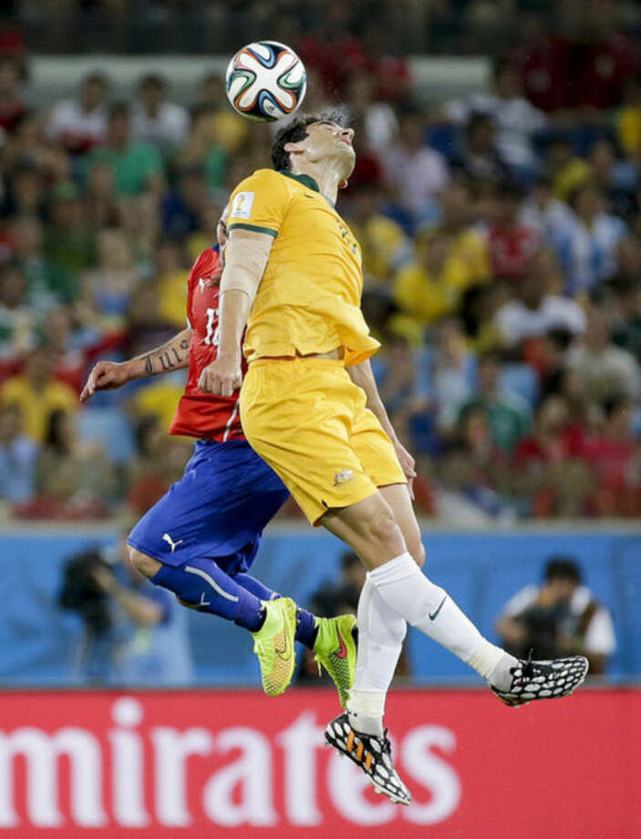 Australia's Mile Jedinak, front, rises above Chile's Gary Medel to win a header during the group B World Cup soccer match between Chile and Australia in the Arena Pantanal in Cuiaba, Brazil, Friday, June 13, 2014. (AP Photo/Felipe Dana)
