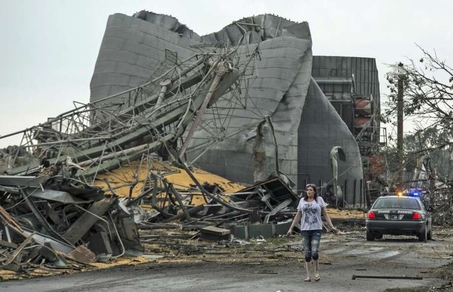 A woman walks down Black Hills Trail road in Pilger, Neb., Monday, June 16, 2014. At least one person is dead and at least 16 more are in critical condition after two massive tornadoes swept through northeast Nebraska on Monday. (AP Photo/Mark 'Storm' Farnik)
