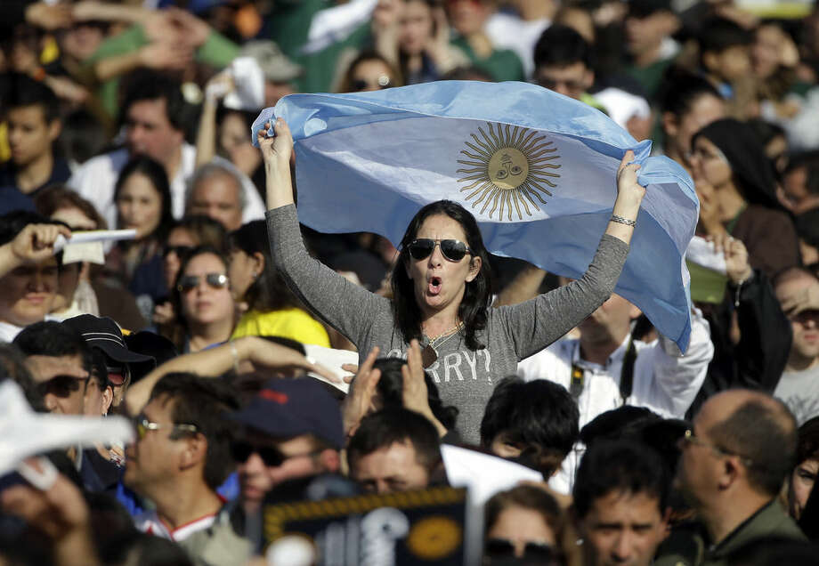 A woman with an Argentine flag waits in the crowd for the start of a mass celebrated by Pope Francis in Asuncion, Paraguay, Sunday, July 12, 2015. Hundreds of thousands have gathered on a huge swampy field called Nu Guazu inside a military base to attend the mass. At this very spot, Pope John Paull II in 1988 canonized Paraguay's first saint, Roque Gonzalez de Santa Cruz, a Jesuit priest that was a missionary to the Guarani people. (AP Photo/Gregorio Borgia)