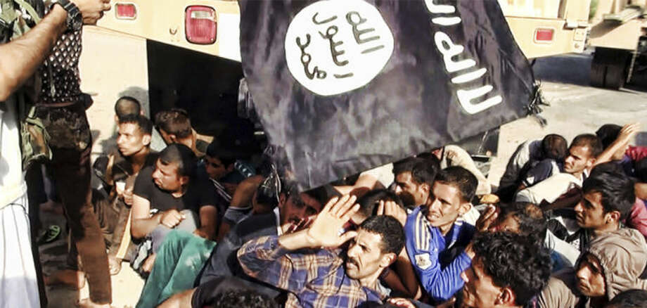 This image posted on a militant website on Saturday, June 14, 2014, which has been verified and is consistent with other AP reporting appears to show militants from the al-Qaida-inspired Islamic State of Iraq and the Levant (ISIL) with captured Iraqi soldiers wearing plain clothes after taking over a base in Tikrit, Iraq. The Islamic militant group that seized much of northern Iraq has posted photos that appear to show its fighters shooting dead dozens of captured Iraqi soldiers in a province north of the capital Baghdad. Iraq's top military spokesman Lt. Gen. Qassim al-Moussawi confirmed the photos' authenticity on Sunday and said he was aware of cases of mass murder of Iraqi soldiers. (AP Photo via militant website)