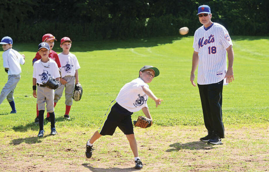 Hour photo/Erik TrautmannNew York Mets third base coach and World Series champion Tim Teufel (18) works with Baseball World campers, including Cameron Agliotta, age 7, on Friday at Taylor Farm Park in Westport.