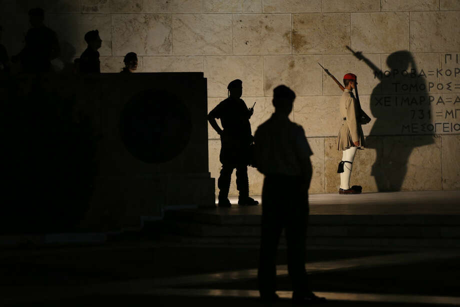 A presidential guard, right, stands guard at the tomb of the unknown soldier as riot police officers guard one of the entrances to the parliament during a demonstration of supporters of the no vote in central Athens, Sunday, July 12, 2015. Greece has another chance Sunday to convince skeptical European creditors that it can be trusted to enact wide-ranging economic reforms which would safeguard its future in the common euro currency. (AP Photo/Emilio Morenatti)