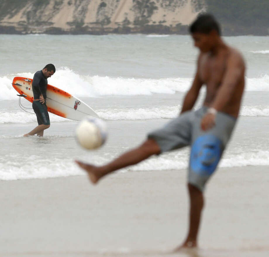 A surfer treks back to the beach as a man kicks a soccer ball in Natal, Brazil, Saturday, June 14, 2014. Natal is one of 12 cities hosting games during the 2014 World Cup soccer tournament. (AP Photo/Julio Cortez)