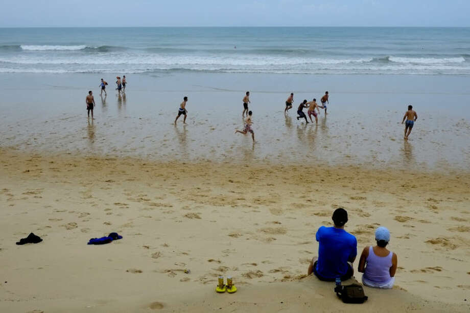 A tourist couple from Atlanta watches a pick-up soccer game on the beach in Natal, Brazil, Sunday, June 15, 2014. Natal is one of 12 cities hosting matches during the 2014 World Cup soccer tournament, including Monday's game between the United States and Ghana in Group G. (AP Photo/Julio Cortez)