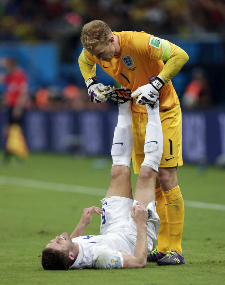 England's goalkeeper Joe Hart (1) applies pressure on Gary Cahill's legs during the group D World Cup soccer match between England and Italy at the Arena da Amazonia in Manaus, Brazil, Saturday, June 14, 2014. (AP Photo/Marcio Jose Sanchez)