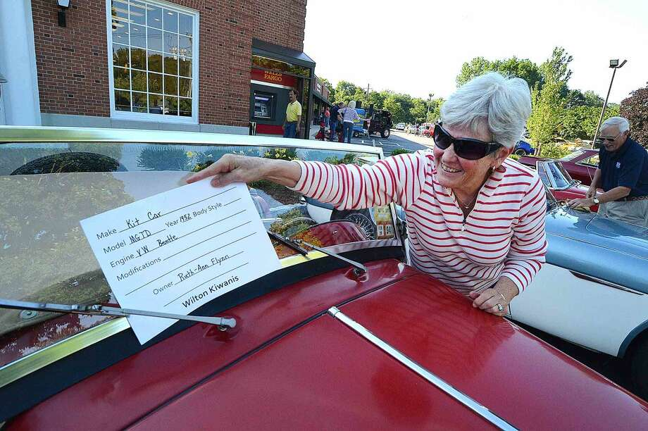 Hour Photo/Alex von Kleydorff Ruth-Ann flynn puts the info card on the windshield of her 1952 MG TD Kit Car at The 15th annual Wilton Kiwanis, Geeb Fleming/Nick Allegretta Memorial Cruise Night