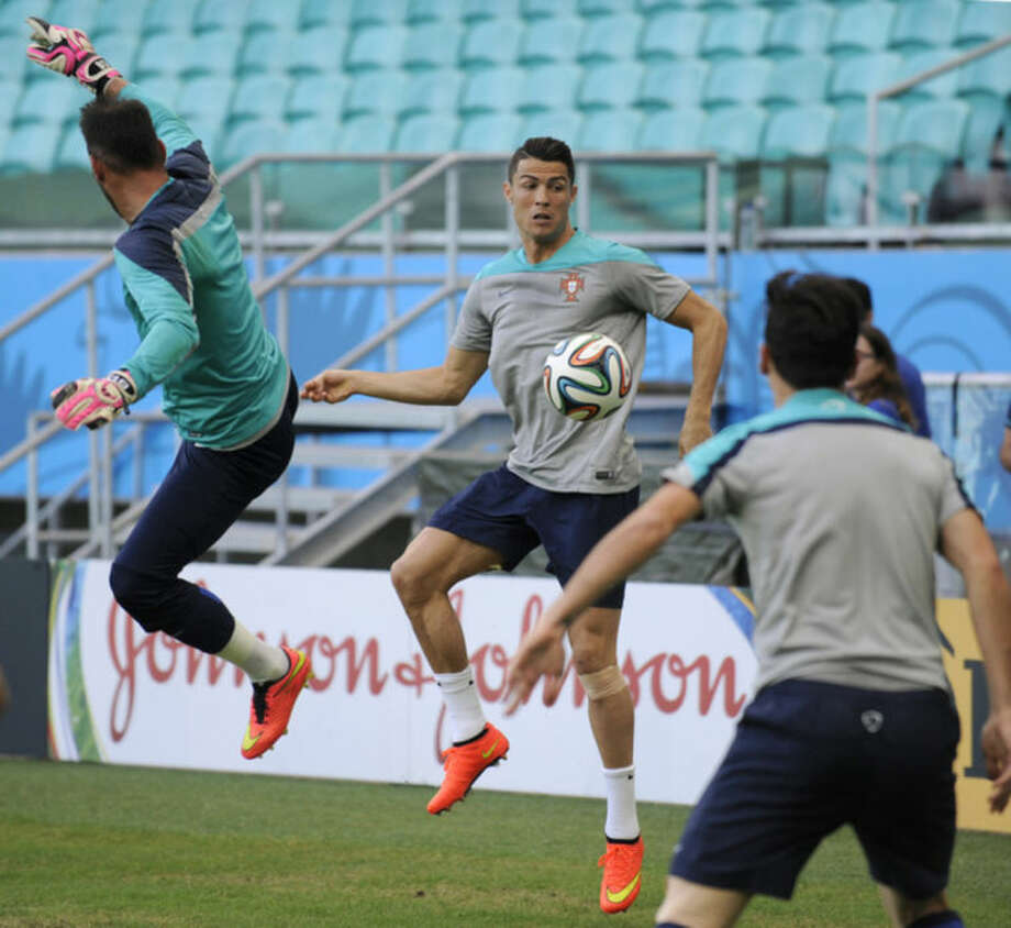 Portugal's Cristiano Ronaldo, center, challenges for the ball with teammates during an official training session the day before the group G World Cup soccer match between Germany and Portugal at the Arena Fonte Nova in Salvador, Brazil, Sunday, June 15, 2014. (AP Photo/Paulo Duarte)