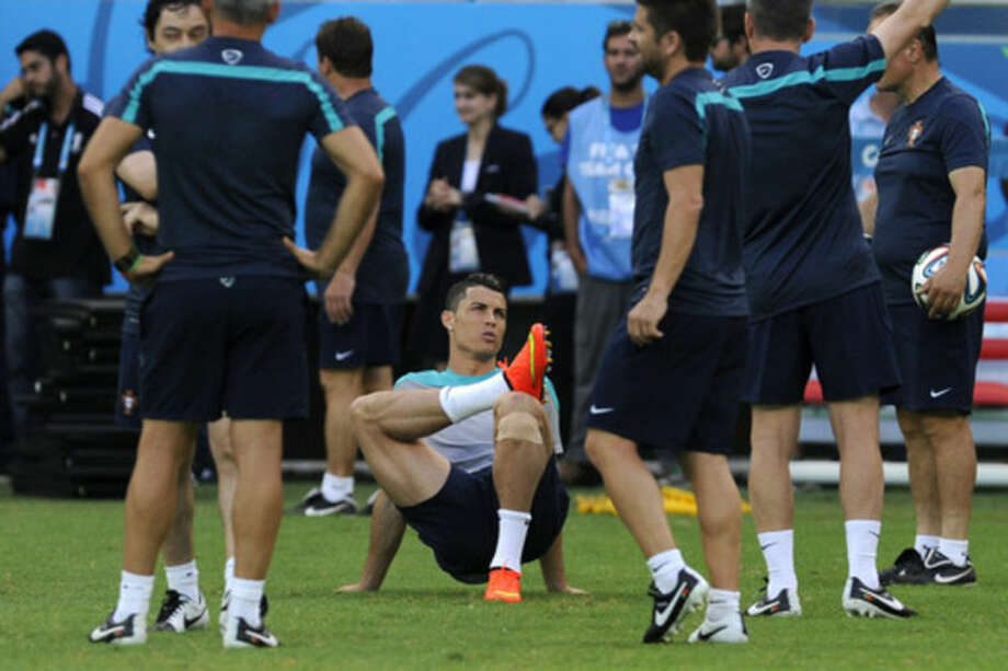 Portugal's Cristiano Ronaldo is surrounded by his teammates prior to an official training session the day before the group G World Cup soccer match between Germany and Portugal at the Arena Fonte Nova in Salvador, Brazil, Sunday, June 15, 2014. (AP Photo/Paulo Duarte)