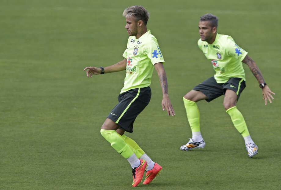 Brazil's Neymar, left, and Dani Alves practice during a training session of the Brazilian national soccer team at the Granja Comary training center in Teresopolis, Brazil, Sunday, June 15, 2014. Brazil plays in group A of the 2014 soccer World Cup. (AP Photo/Andre Penner)